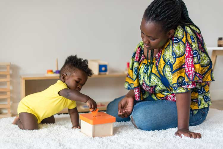 Toddler playing with Montessori coinbox