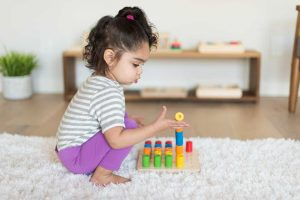 toddler playing with montessori pegboard