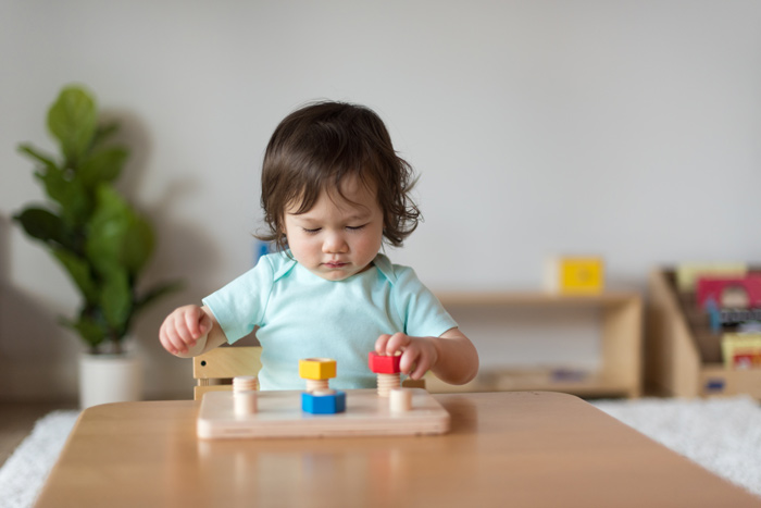 Baby playing with Montessori toy